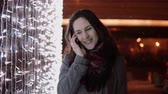 celebração : young attractive woman talking on the phone in the falling snow at Christmas night standing near lights wall, Stock Footage