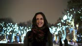 movimentar se : attractive woman at snowy Christmas night smiles looking at the camera in front of park trees decorated sparkling lights