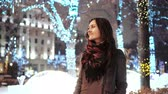urlop : attractive woman at snowy Christmas night smiles looking at the camera in front of park trees decorated sparkling lights