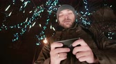 Боке : young handsome man using smartphone at Christmas night standing under a tree decorated with sparkling lights