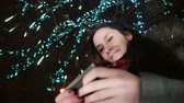 ниже : young attractive woman using smartphone at snowy Christmas night standing under a tree decorated with sparkling lights Стоковые видеозаписи