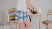 šortky : Happy young woman wearing pajamas preparing flakes for breakfast and dancing in light kitchen. Having fun in morning. Dostupné videozáznamy