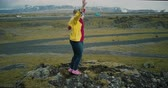 helicóptero : Aerial view of the two happy woman in bright clothes dancing on the top of mountain. Tourist in lava field in Iceland. Stock Footage