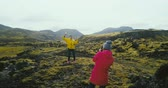 filmagens : Copter filming the tourists having the photoshoot in the mountains. Two woman taking photo in lava field in Iceland. Vídeos