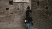 explorers : Young beautiful tourist is in Palatine Hill in Rome, Italy, considering an antique aesthetic wall-painting of ancient. Stock Footage