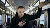osobitost : Young handsome man uses the smartphone in public transportation, in metro. Male surfing the Internet with touchscreen
