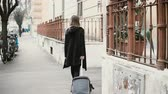 chegar : Back view of attractive woman with suitcase walking on the street. Businesswoman are going through the arch.