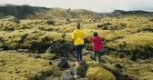 helicóptero : Aerial view of two woman walking on the lava field in Iceland. Tourists exploring the meadow covered moss, hiking.