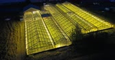 экологический : Beautiful aerial view of the large greenhouse with light in it. Ecological farm shining in the dark night.