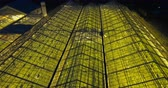 экологический : Aerial close up view of greenhouse with light inside. Copter flying over the organic planting in the night.