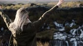 flow : Freedom: back view of young happy woman looking at Barnafoss waterfall in Iceland, raising hand and jumping of joy. Stock Footage