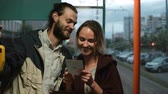 card game : Young couple standing near the window in tram or bus and reading from the card. Man and woman using public transport. Stock Footage