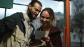 questões : Man and woman holding the card from box and reading something. Young couple in hugging in tram in evening.