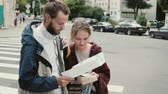 questão : Happy young man and woman holding the box with cards and map. Tourists couple playing board game, searching direction Stock Footage