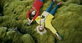 unidade : Aerial top view of the two happy woman lying on the soft moss in lava field in Iceland. Tourists resting on nature.
