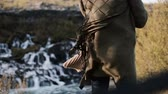бахрома : Close-up view of Barnafoss waterfall in Iceland and female back. Fringe from jacket of young woman waves on wind.