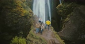 flow : Aerial view of the tourists in Gljufrabui waterfall in Iceland. Copter moving away from friends, selfie on drone. Stock Footage