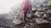 chuva : Back view of young tourist woman climbing on the mountain in rainy day. Female exploring the new place. Slow motion.