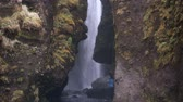 chuva : Man and woman in raincoats exploring the famous sight in Iceland. Beautiful view on Gljufrabui waterfall.