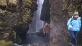 chuva : Two young tourists exploring the powerful waterfall Gljufrabui in Iceland. Man and woman in raincoat walking in rain. Vídeos