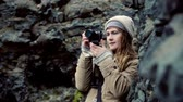 contraste : Young beautiful woman holding camera and taking photos in the mountains. Traveling female filming on the nature. Stock Footage