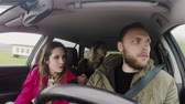 életmód : Young happy people traveling by car together. Friends trying to find the way, man driving the vehicle. Stock mozgókép