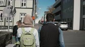 молодежная культура : Back view of young stylish couple walking in downtown together. Man and woman holding hands and exploring the city.