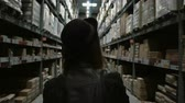 bom : Back view of young woman with cart walking through the high shelves with goods for repair in big warehouse.