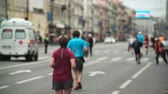 Питер : Crowd of people are running marathon on road in city center. Men and women in sportswear participate in race on track Стоковые видеозаписи