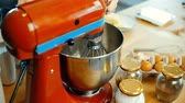 słodycze : Close-up view of young female preparing dough in the bowl. Woman turns on the mixer for blending ingredients.