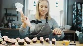 mão humana : Young beautiful woman decorating the little cupcakes with cream from pastry bag. Blonde confectioner preparing an order. Stock Footage