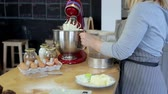 queque : Young blonde woman blending the cream in a bowl. Attractive female turning on the mixer, cooking the dessert in kitchen. Vídeos