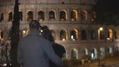 utazási : Back view of young man and woman standing near the Colosseum in Rome, Italy and hugging together.