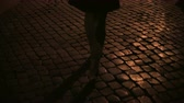medo : Close-up view of female feet walking through the deserted street in the evening with pavement road. Vídeos