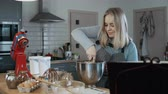 dona de casa : Young beautiful woman mixing the ingredients in a bowl, preparing dough for baking. Blonde female in kitchen. Stock Footage