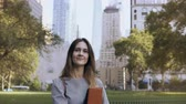 downtown : Portrait of young smiling woman in New York, USA. Beautiful businesswoman holding the documents and looking at camera. Stock Footage