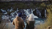 даты : Back view of young traveling couple standing in mountains near the waterfalls in Iceland and taking photo on smartphone