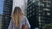 hırs : Back view of young businesswoman holding the documents and going to office building in New York, USA. Slow motion.