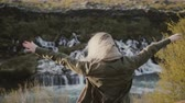 flow : Freedom: young traveling woman looking on waterfalls in Iceland and raising hands up, feeling happy. Stock Footage