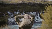 chuva : Back view of young traveling woman standing in mountains valley and looking on waterfalls in Iceland alone.