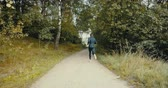tranquilo : Sportsman running to a forest road opening. Drone back view. Sprinter enjoying quiet autumn countryside pathway. Vídeos