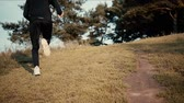 мотивированы : Slow motion runner going uphill to a forest. Low angle back view. Young athlete exploring fall countryside landscapes.