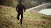 lightness : Slow motion. Man running down fall grass hill. Camera follows runner enjoying atmospheric fall nature distant forest. Stock Footage