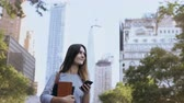 orgulho : Portrait of young businesswoman holding the notebook and using the smartphone. Female manager chatting with colleagues. Stock Footage