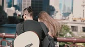 музыкант : Back view of young beautiful couple standing on the bridge, enjoying the view of Chicago, America. Man with guitar. Стоковые видеозаписи