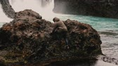 escandinavo : Young traveling man with camera exploring Iceland. Tourist climbs on the rock near the waterfalls and raises hands.