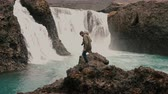 meditativo : Young handsome man with camera walking alone in mountains valley near the powerful waterfall in Iceland.