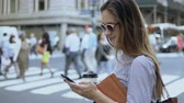 downtown : Young beautiful businesswoman using the smartphone near the traffic road. Female holding documents and coffee cup. Stock Footage