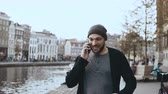 edge : Happy European man walking, talking on the phone. 4K. Casual creative bearded man walks on river embankment in old town. Stock Footage
