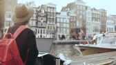 escritor : 4K 30s happy businesswoman working with laptop. Amsterdam. Lady with red backpack sits on beautiful river embankment.